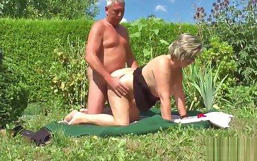 German Grandpa and Grandma Fellow-feeling a amour Abiding in Garden